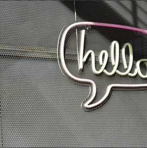 """Photo of a neon sign against a wall in a speech bubble with the word """"hello"""""""